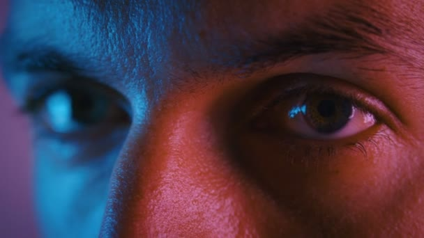 Close up eyes of male in multicolor neon light. Portrait of a young man at night during the party in neon lights.