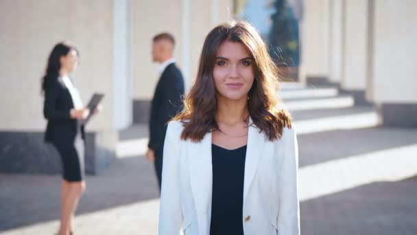 Portrait of Pretty Young Businesswoman Standing in the City near Office Building. Looking Happy and Satisfied. White Jacket Dressed. Business People Communicating in the Background.