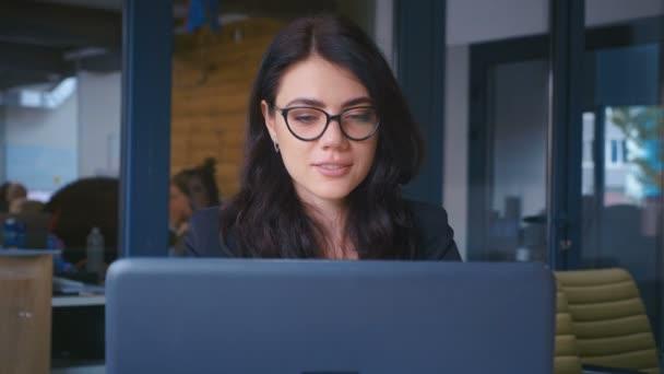 Atraktivní mladá podnikatelka pracující na notebooku v moderní kanceláři.