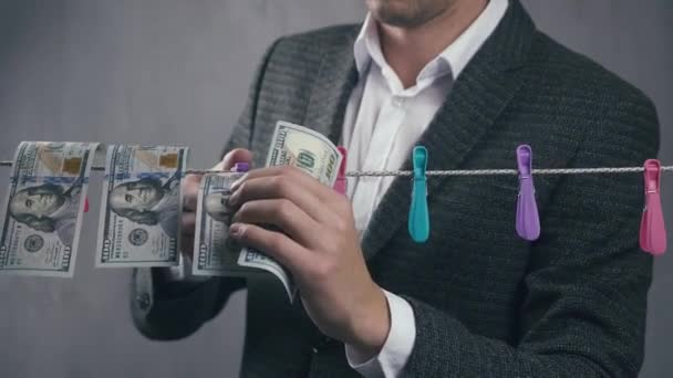 Male criminal launders money. A man dries dollar bills on a rope. Economic crime concept.