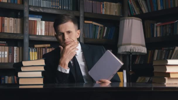 Businessman in classical suit sitting in library searching for information in books