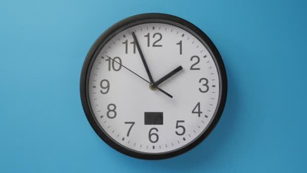 Bílé kancelářské hodiny visí na modré zdi.