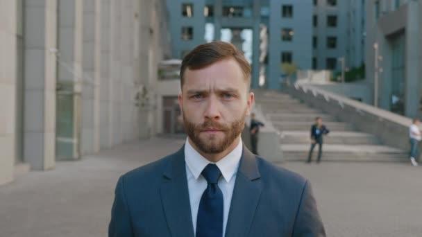 Portrét sebevědomého vousatého podnikatele v obleku procházky do centra na ulicích obchodní čtvrti. Důvěryhodný podnikatel jde do práce v moderní kancelářské budově.