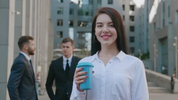 Porträt einer jungen lächelnden Geschäftsfrau mit Kaffeetasse, die draußen in der Nähe eines modernen Bürogebäudes steht. Schöne brünette Mitarbeiterin lächelt in die Kamera vor dem Hintergrund der Innenstadt
