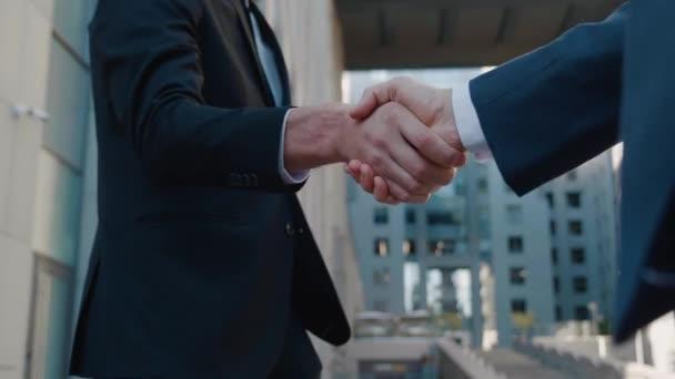 Detailní záběr dvou obchodníků si potřást rukou při schůzce, souhlasit s dohodou nebo pozdravit. Potřesení rukou dvou úspěšných podnikatelů uzavírajících dohodu. Kancelářská budova na pozadí. Obchodní čtvrť.