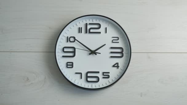 Bílé kancelářské hodiny visí na zdi. Včasná