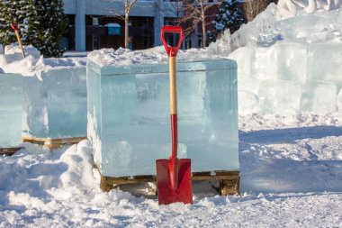 A red shovel stands near a block of pure transparent ice