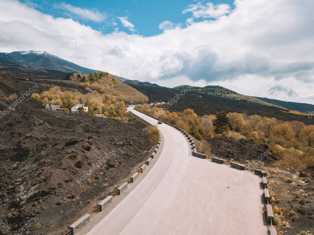 Beautiful aerial view on the empty road to Etna volcano that can be seen on the horizon.