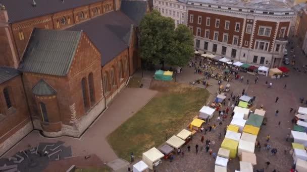 Schöne Luftaufnahme des Hauptplatzes der Rigaer Altstadt (Domplatz) mit lokalem Markt und Menschen, die sich auf das nationale Ligo -Fest vorbereiten.