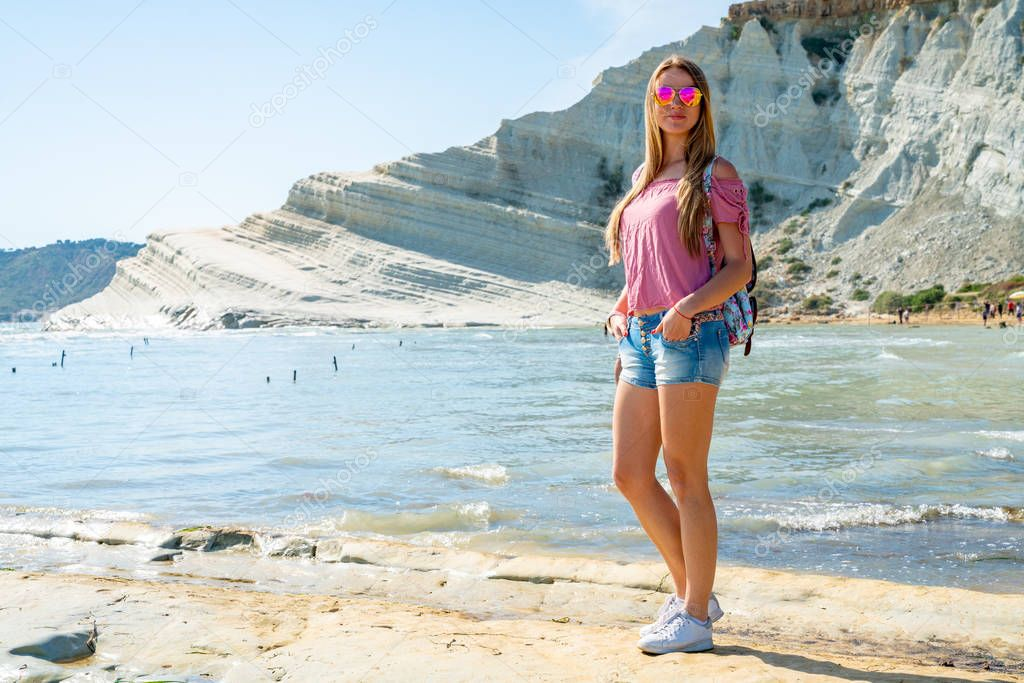 Young girl exploring Turchi white cliffs on Sicily island.