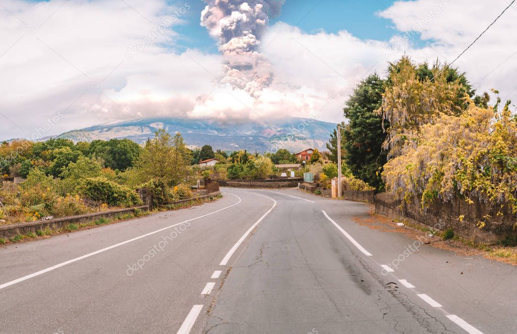 Eruption of the Etna volcano on the horizon of the lonely road on Sicily. Beautiful and wild nature.