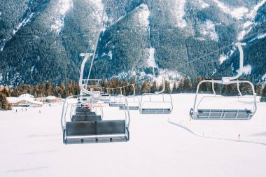 Ski lefts and cable cars in the Alps winter resort. People going up for skiing and snowboarding. Austrian Alps.