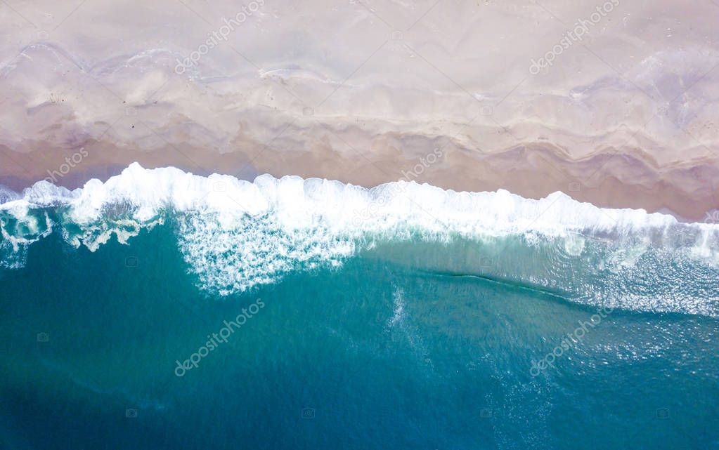 Aerial view of the ocean waves washing on the coast of the Pacific ocean