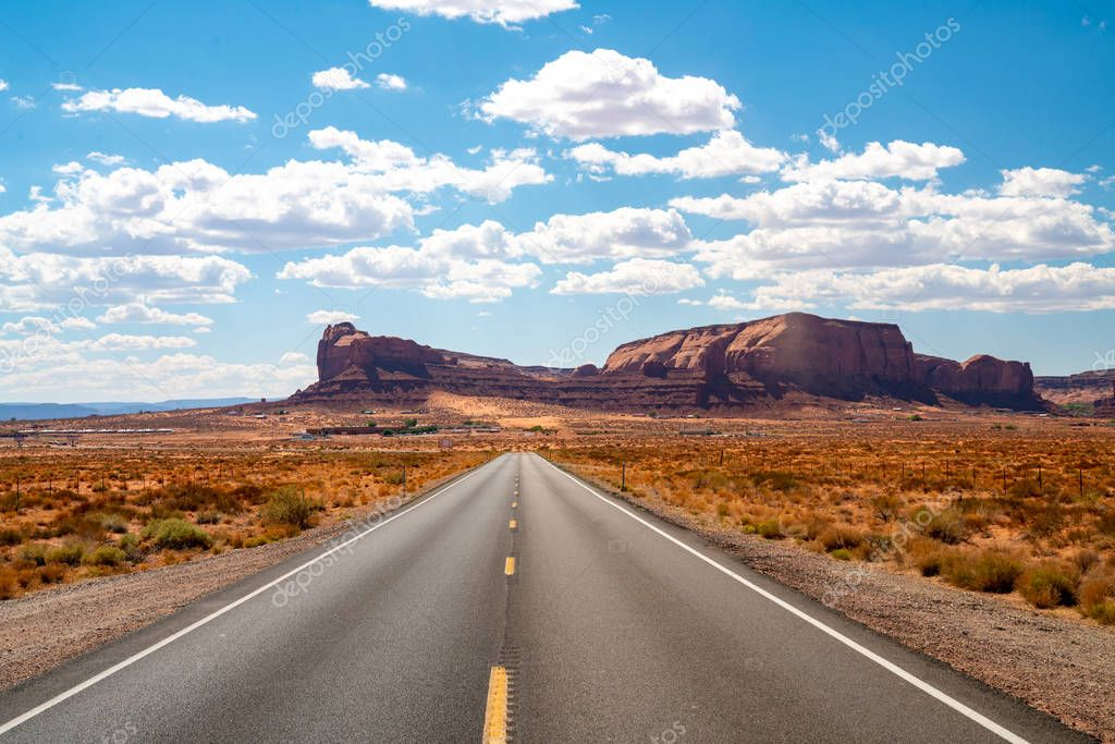 Endless infinite road that goes through the Monument Valley National park with amazing rock formations.