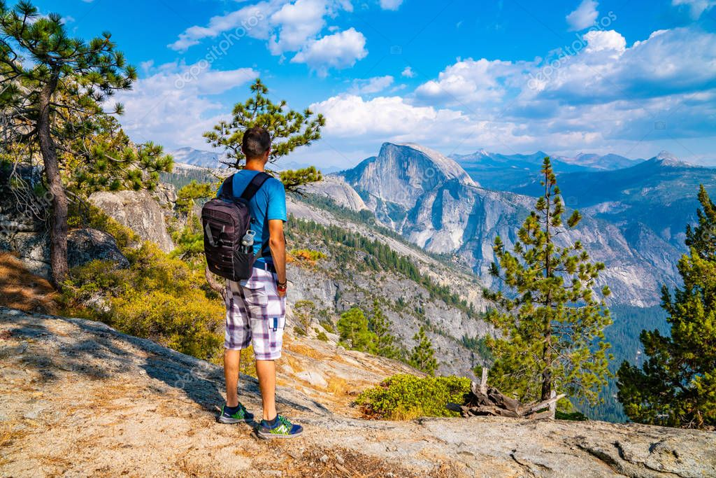 Young man hiking in the Yosemite National park. Exploring the valley, waterfall and half dome trails.