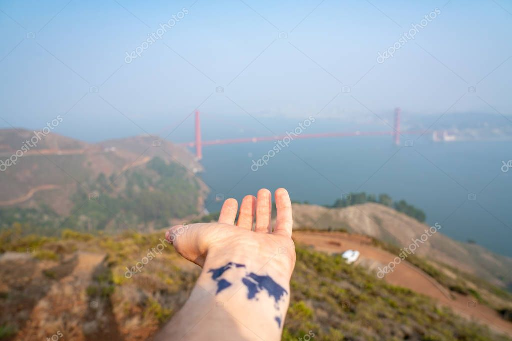 Explore the world in California. Young man with a tattoo of the world on his hand. Beautiful world.