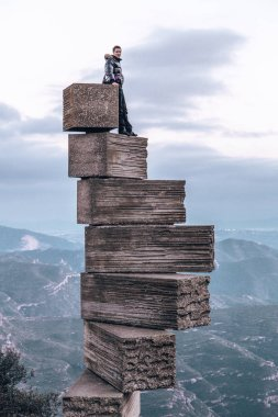Monserrat, Spain. March 10, 2019. Young man standing on top of the world near Montserrat in Spain. stock vector