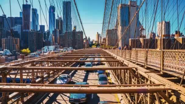 Gyönyörű időeltolódás a Brooklyn hídról mozgásban. Autók és emberek haladnak át a hídon Manhattan szigetéről Brooklynba.