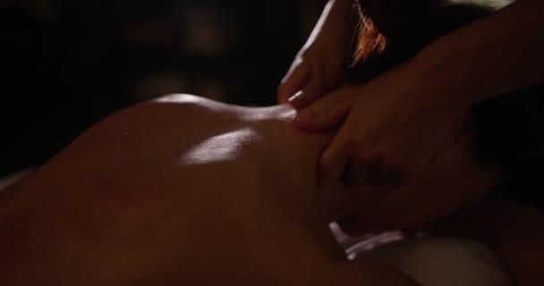 Masáž šíje zblízka, ženských rukou masíruje tělo ženy v pomalém pohybu