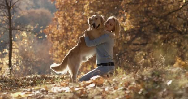 young beautiful Woman in the park with her retriever labrador dog. Autumn background