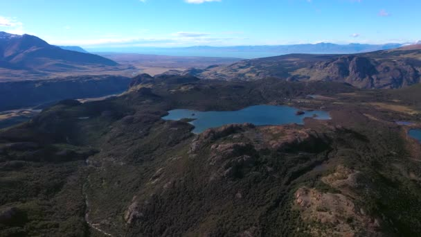 Panoramic aerial drone view of blue aquamarine lakes, rivers, Andes mountains, and green tree forest in Patagonia, Argentina