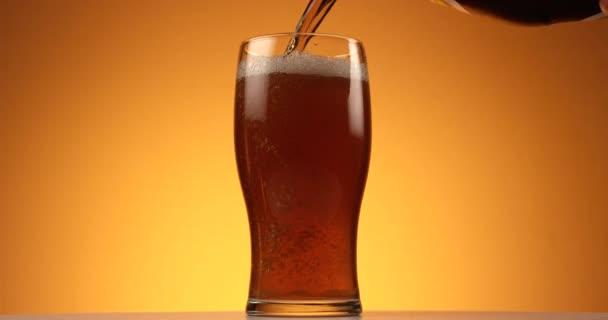 Pivo se vlije do sklenice na žlutém pozadí. Pomalý pohyb zblízka, záběr na červený 6k fotoaparát