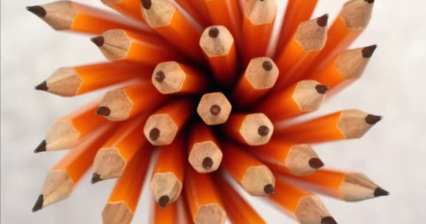Yellow coated pencils rotating in slow motion. Close up top view, shot on RED 6K camera