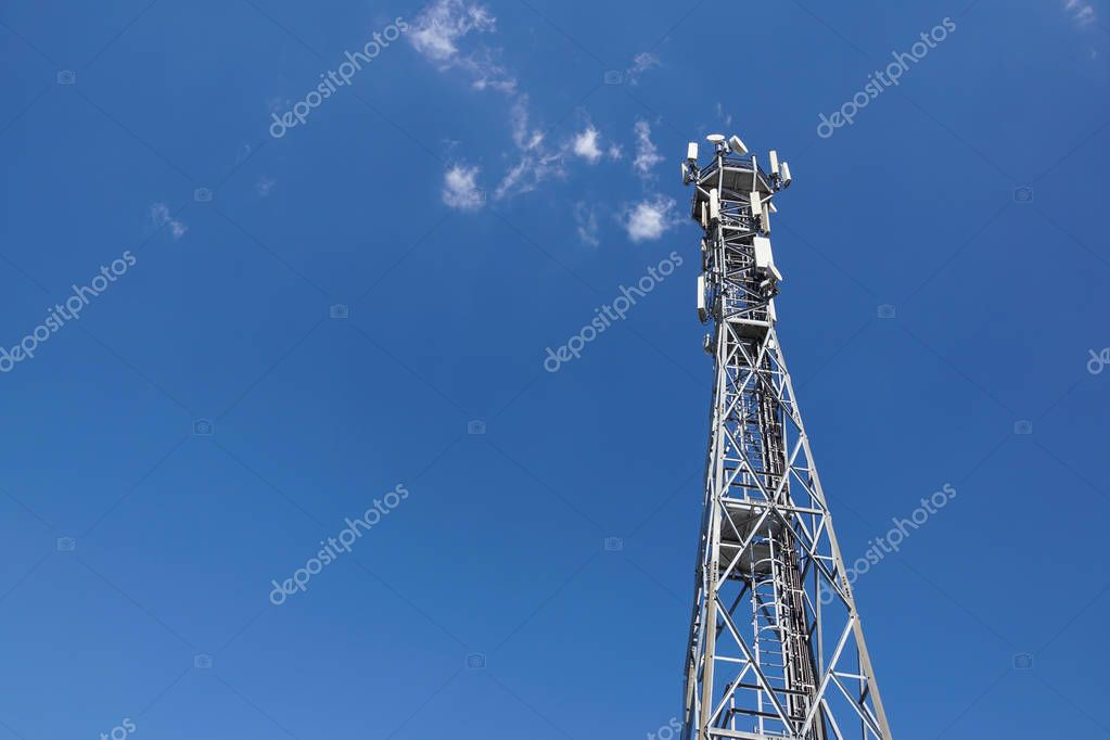 Telecommunication tower with antennas with blue sky .