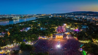 BUDAPEST, HUNGARY - AUGUST 12, 2018: Aerial panoramic photograph of Sziget Festival and main stage with the skyline of Budapest at background at blue hour. Sziget Festival is the biggest music festival in Europe
