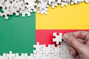Benin flag  is depicted on a table on which the human hand folds a puzzle of white color.