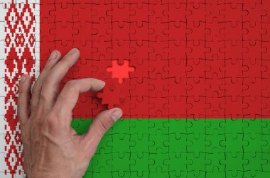 Belarus flag  is depicted on a puzzle, which the man's hand completes to fold.