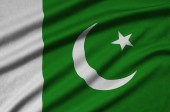 Fotografie Pakistan flag  is depicted on a sports cloth fabric with many folds. Sport team waving banner