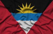 Antigua and Barbuda flag  is depicted on a sports cloth fabric with many folds. Sport team waving banner