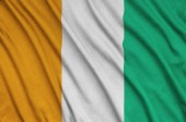 Ivory Coast flag  is depicted on a sports cloth fabric with many folds. Sport team waving banner