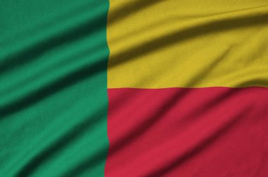 Benin flag  is depicted on a sports cloth fabric with many folds. Sport team waving banner