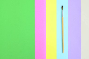 A new paint brush lie on texture background of fashion pastel pink, blue, green, yellow, violet and beige colors paper in minimal concept. Abstract trendy pattern.