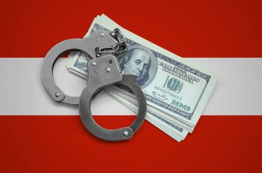 Austria flag  with handcuffs and a bundle of dollars. Currency corruption in the country. Financial crimes.