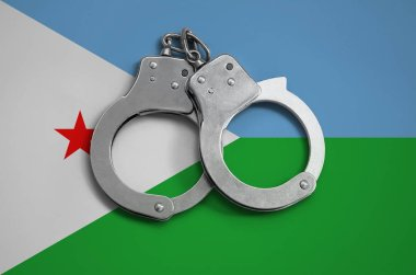 Djibouti flag  and police handcuffs. The concept of observance of the law in the country and protection from crime.