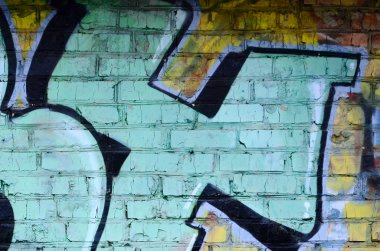 Fragment of graffiti drawings. The old wall decorated with paint stains in the style of street art culture. Colored background texture.