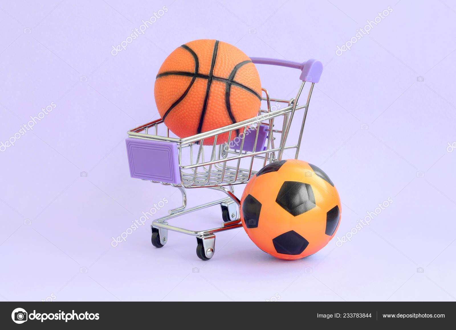 fece38e31 Bola de basquete e futebol laranja no carrinho de compras na violeta. O  conceito de venda de equipamentos esportivos