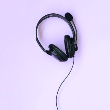 Black headphones lies on a colorful pastel violet background. Music listening concept. Flat lay top view
