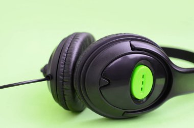 Black headphones lies on a colorful pastel green background. Music listening concept