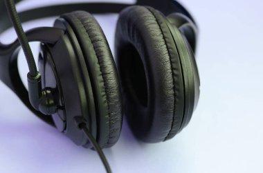 Black headphones lies on a colorful pastel violet background. Music listening concept
