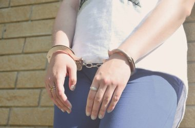 Fragment of a young criminal girl's body with hands in handcuffs against a yellow brick wall background. The concept of detaining an offender of a female criminal in an urban environment