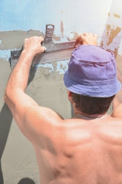 Fifty years old manual worker with wall plastering tools renovating house. Plasterer renovating walls and corners with spatula and plaster. Wall mash installation. Construction finishing works