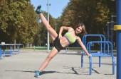 Mladý bělošský sportovkyni v zářivě zelené sportovní oblečení cvičit nohy jezdí na sportovní gym pro aktivní rekreaci. Letní sporty a zdravého životního stylu