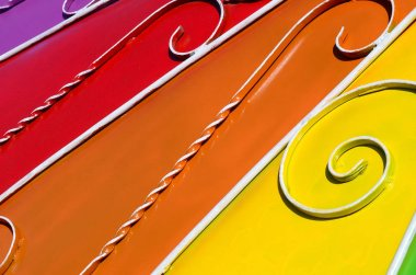 Metal texture of a piece of colored wall with a forged pattern. Rainbow colors