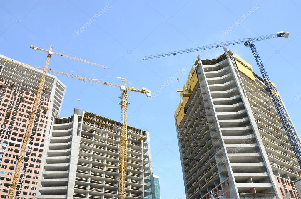 Construction site. High rise multi storey buildings under construction. Tower cranes near buildings