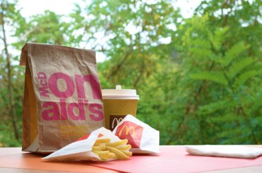 McDonald's take away paper bag and junk food on wooden table outdoors