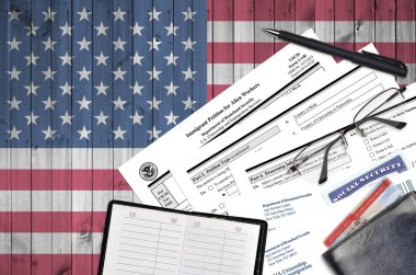 USCIS form I-140 Immigrant petition for alien workers lies on flat lay office table and ready to fill. U.S. Citizenship and Immigration services paperwork concept. Top view